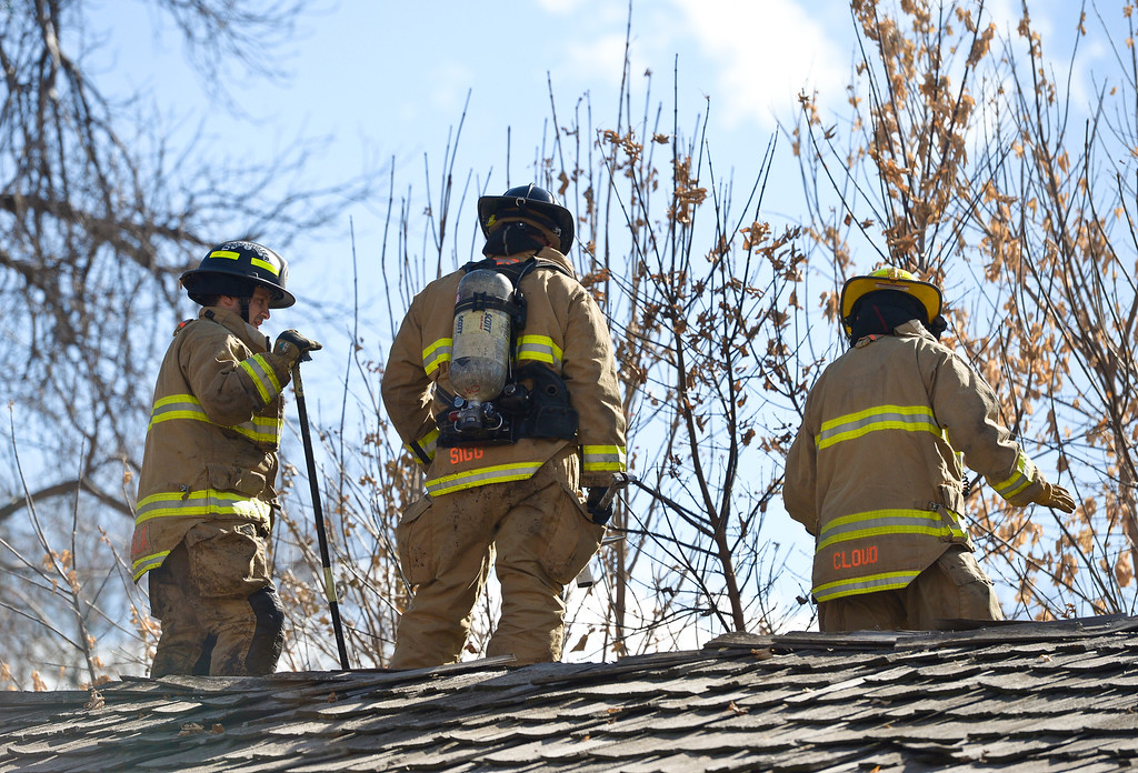 . LONGMONT, CO - NOVEMBER 6: Longmont firefighters check the roof after extinguishing a fire between two multi-car garages behind the apartment building at 1611 Warren Ave., Nov. 6, 2018. (Photo by Lewis Geyer/Staff Photographer)