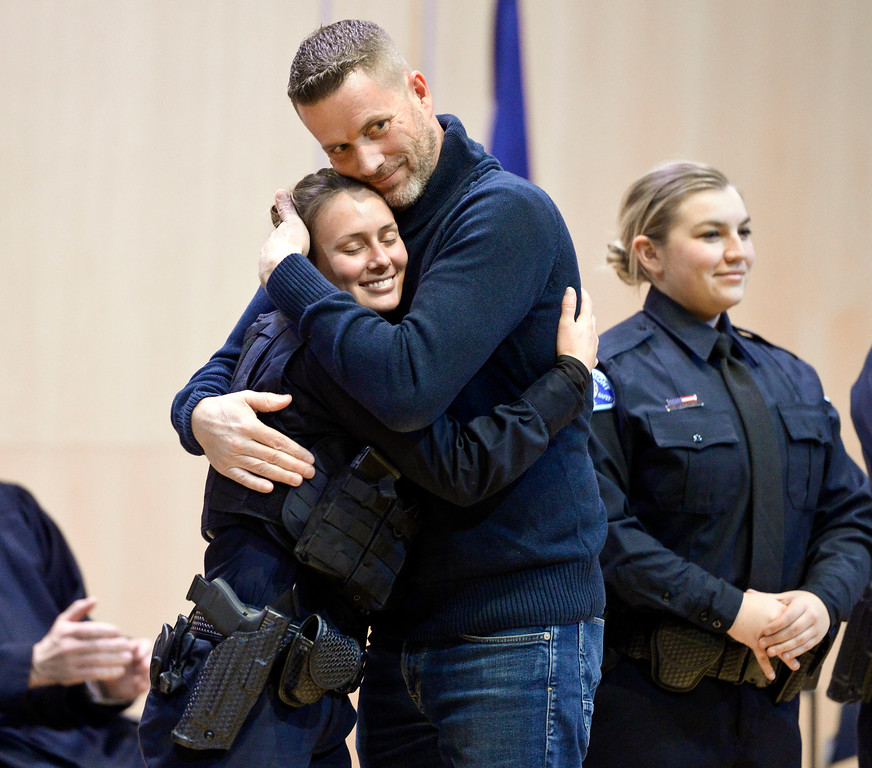 . LONGMONT, CO - JANUARY 14: Don Terry hugs his daughter Mikenzie Terry after pinning her badge on during the Public Safety Recognition Ceremony January 14, 2019 in the Stewart Auditorium at the Longmont Museum and Cultural Center. Next to Don Terry is new police officer Savanah Vowers. Mikenzie Terry was one of ten new police officers sworn in during the ceremony. To view more photos visit timescall.com. (Photo by Lewis Geyer/Staff Photographer)