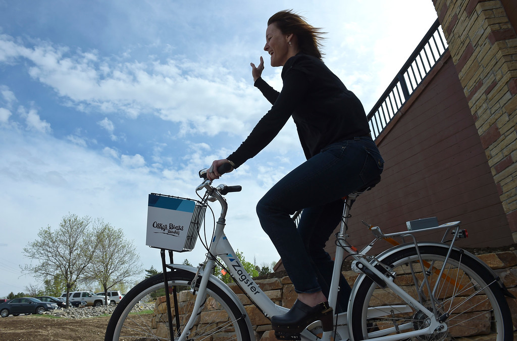 . Oskar Blues\' Diana Ralston waves as she returns from a short ride on a Zagster bike during a dedication ceremony for the new Diagonal underpass and Longmont\'s bike share program Thursday. To view a slideshow visit www.timescall.com. Lewis Geyer/Staff Photographer April 20, 2017