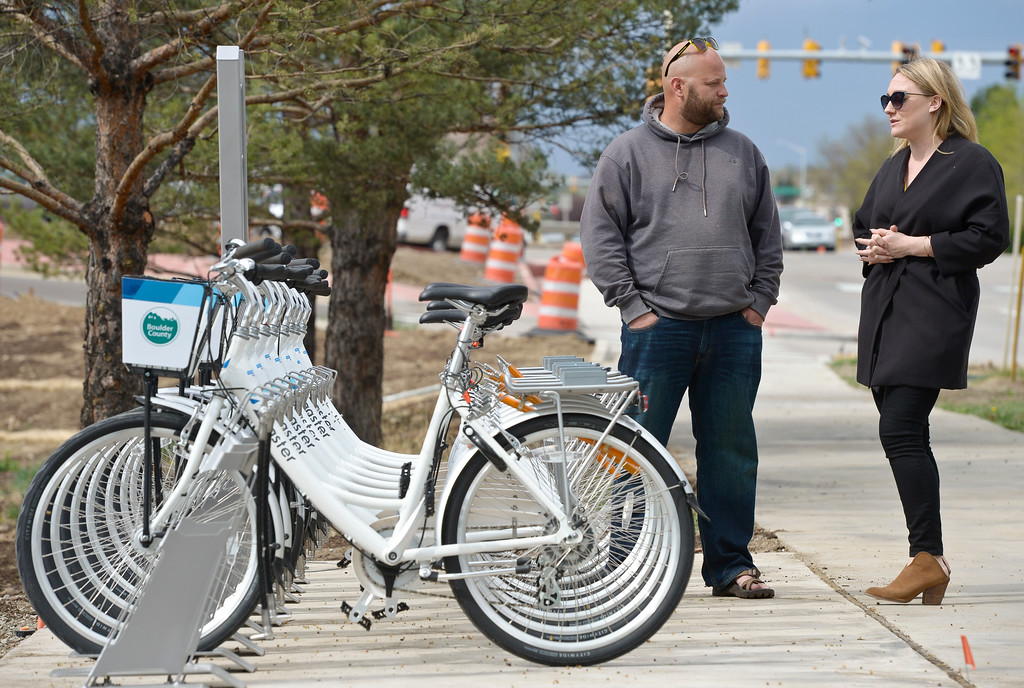 . Ashley Collins, of Zagster, and Brad Smith stand near a rack full of Longmont Bike Share bikes before a dedication ceremony for the new Diagonal underpass and the bike share program Thursday. To view a slideshow visit www.timescall.com. Lewis Geyer/Staff Photographer April 20, 2017