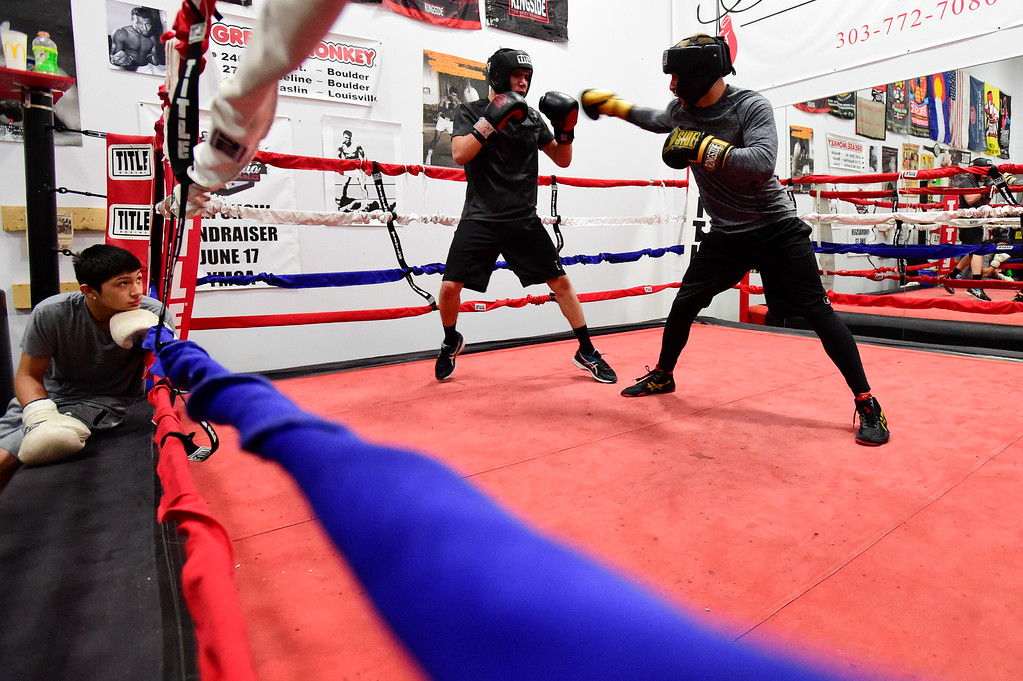 . Jose Campos, 16, left, watches as Cesar Perez, 16, spars with Russ Ulmer at the YMCA in Longmont, Colorado on May 2, 2018. (Photo by Matthew Jonas/Staff Photographer)