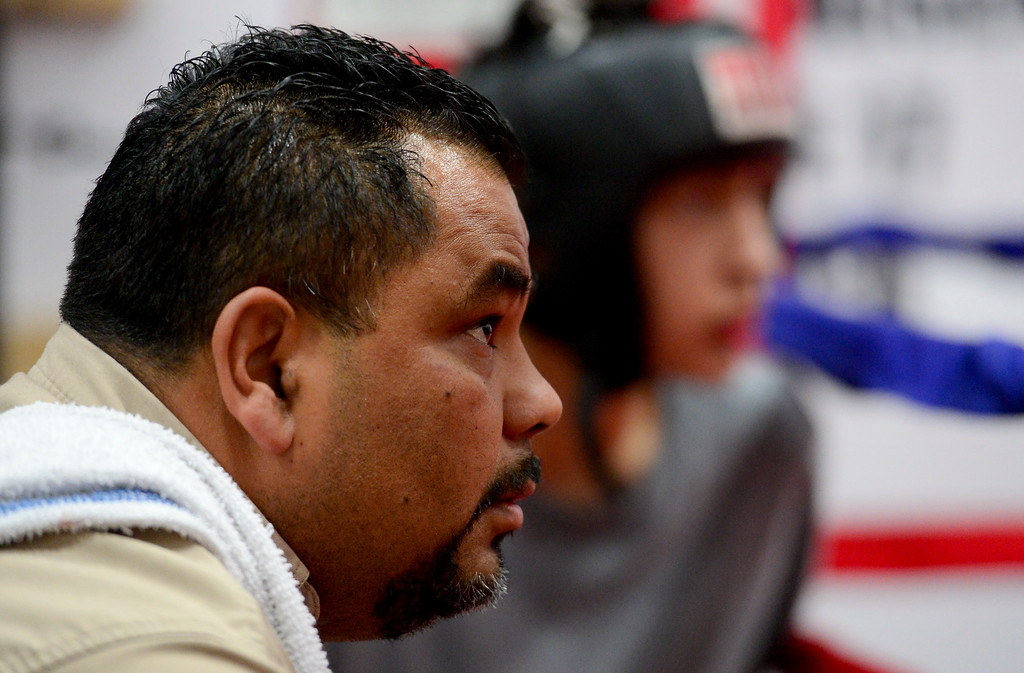 . Coach and Trainer Randy Lopez, left, and boxer Jose Campos, right, watch as Damian Campos, 13, and Angel Vasquez, 14, spar at La Familia boxing at the YMCA in Longmont, Colorado on May 2, 2018. (Photo by Matthew Jonas/Staff Photographer)