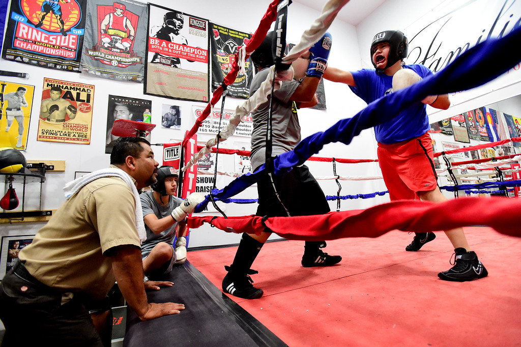 . Coach and Trainer Randy Lopez and boxer Jose Campos watch as Damian Campos, 13, right, and Angel Vasquez, 14, spar at La Familia boxing at the YMCA in Longmont, Colorado on May 2, 2018. (Photo by Matthew Jonas/Staff Photographer)
