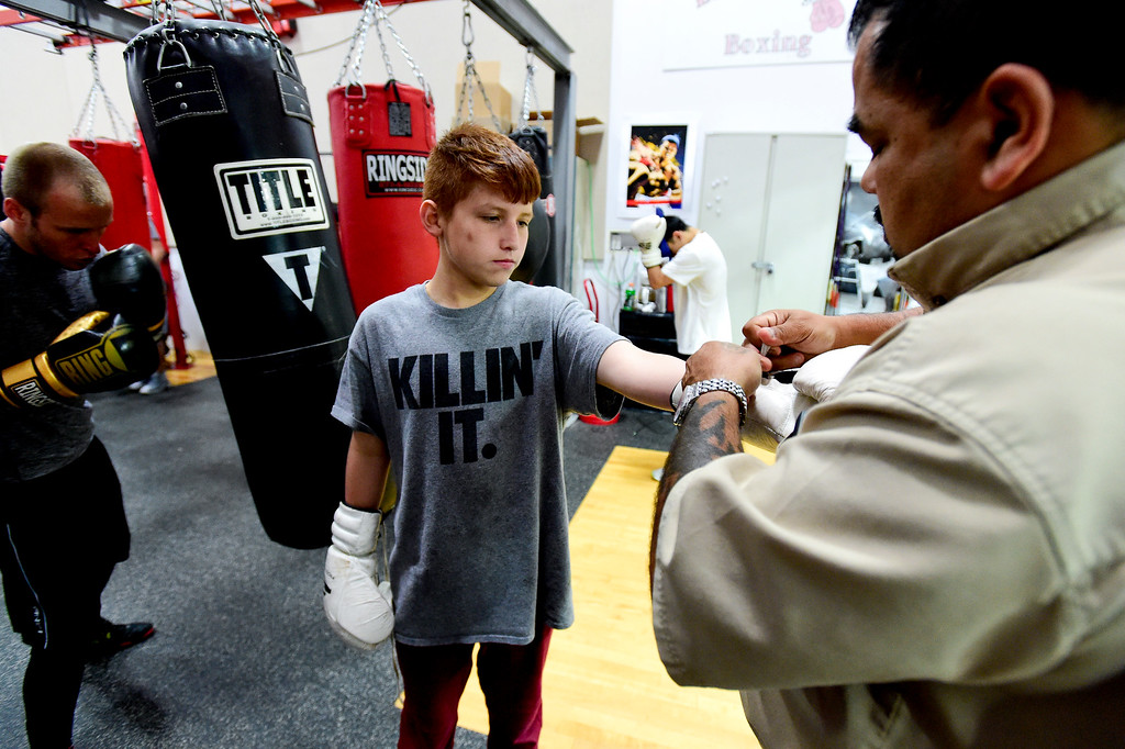 . Coach and Trainer Randy Lopez helps boxer Oscar Loya, 13, put on his gloves at La Familia boxing at the YMCA in Longmont, Colorado on May 2, 2018. (Photo by Matthew Jonas/Staff Photographer)
