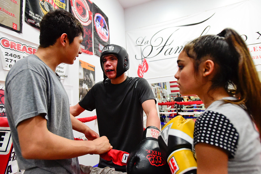 . Jose Campos, 16, left, talks with Cesar Perez, 16, as Brooke Ochiuzzo, 12, looks on in between sparing rounds at La Familia boxing at the YMCA in Longmont, Colorado on May 2, 2018. (Photo by Matthew Jonas/Staff Photographer)