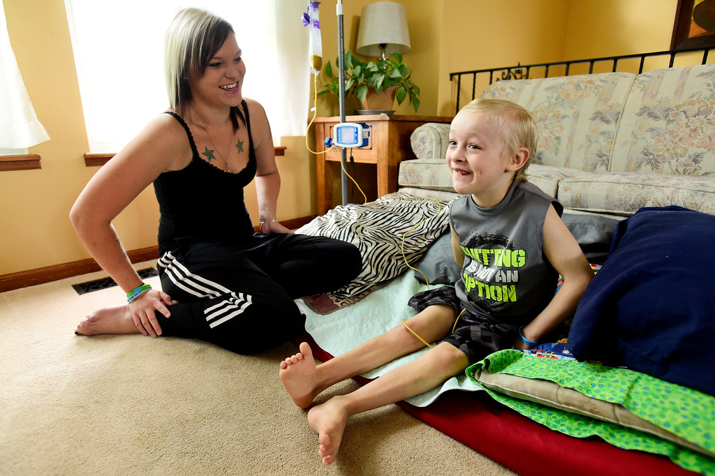. Riley Heasley, 8, and his mother Erin Heasley share a laugh while he eats from a feeding tube at their home in Longmont on Aug. 11, 2017. Riley has Pantothenate Kinase-Associated Neurodegeneration, a rare inherited neurological movement disorder, and is unable to walk or talk. (Photo by Matthew Jonas/Times-Call)