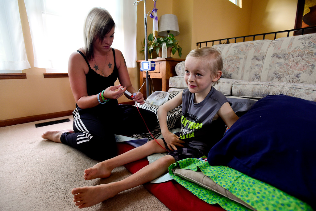 . Erin Heasley injects a medication into a feeding tube for her son Riley Heasley, 8, as he watches TV in Longmont on Aug. 11, 2017. Riley has Pantothenate Kinase-Associated Neurodegeneration, a rare inherited neurological movement disorder, and is unable to walk or talk. (Photo by Matthew Jonas/Times-Call)