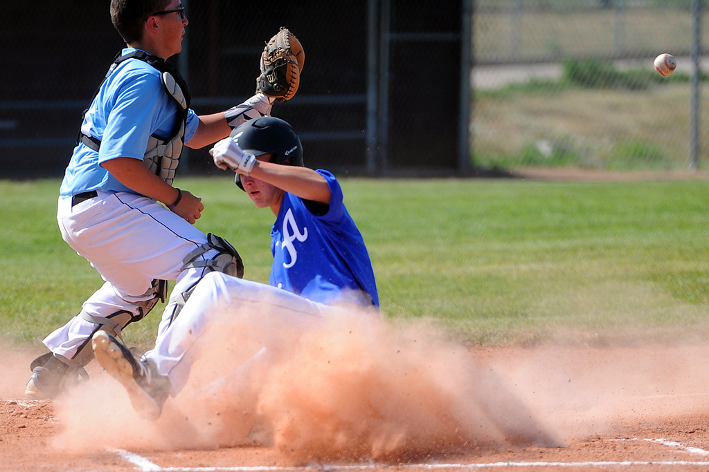 . Anthony Bartelson slides safely into home as catcher Gabe Shelley gets ready to receive the throw during a Loveland Aces scrimmage on Tuesday, June 12, 2018 at Brock Field in Loveland, Colorado. (Sean Star/Loveland Reporter-Herald)
