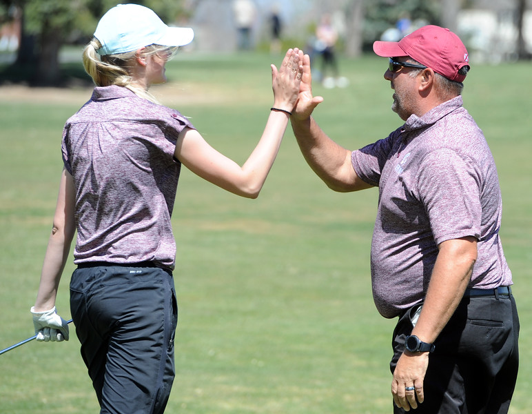 Berthoud's Kyra McDonald, left, high-fives coach Troy Diffendaffer during the Loveland Invitational on Wednesday at The Olde Course at Loveland. (Sean Star/Loveland Reporter-Herald)