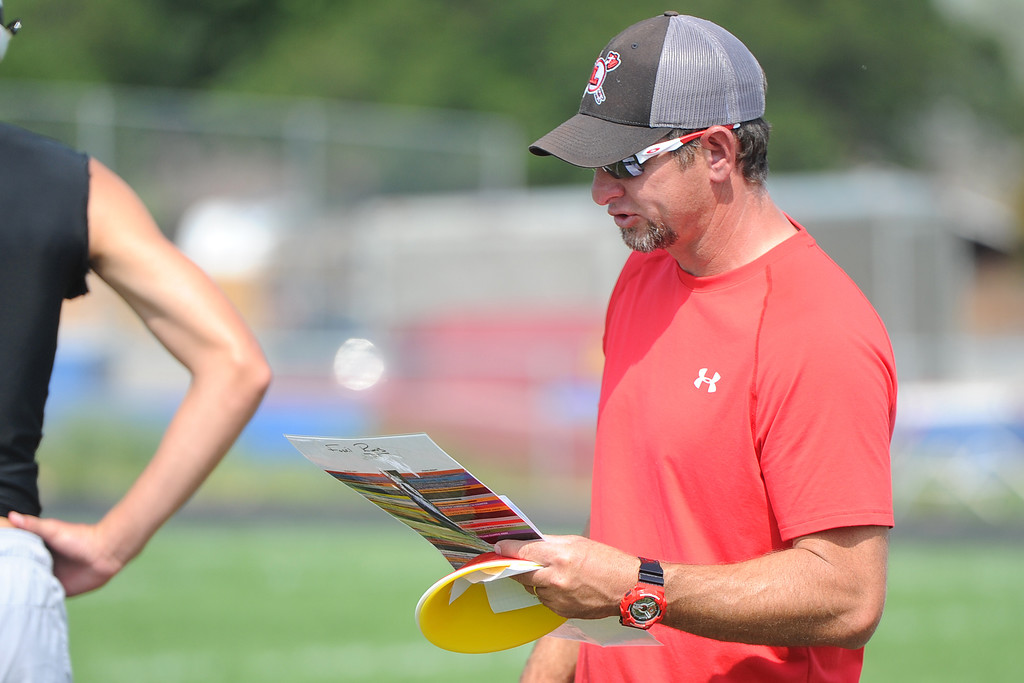 . Assistant coach Jeff Mauck reads from a play sheet during the Loveland football team�s practice Thursday, Aug. 16, 2018 at Loveland High School. (Sean Star/Loveland Reporter-Herald)