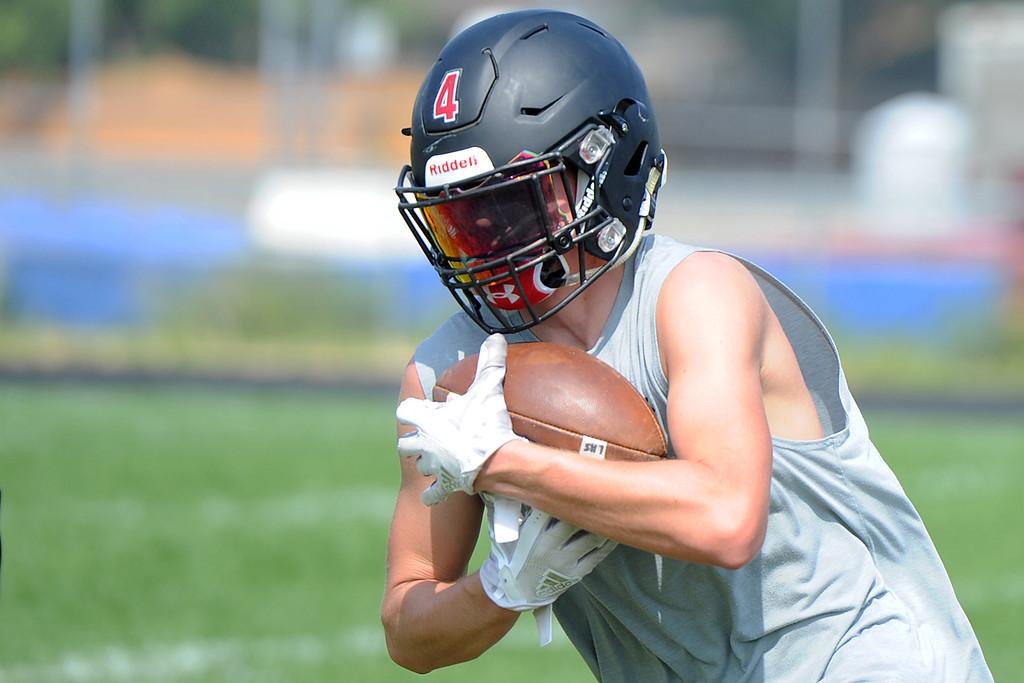 . Cody Rakowsky takes a handoff during the Loveland football team�s practice Thursday, Aug. 16, 2018 at Loveland High School. (Sean Star/Loveland Reporter-Herald)