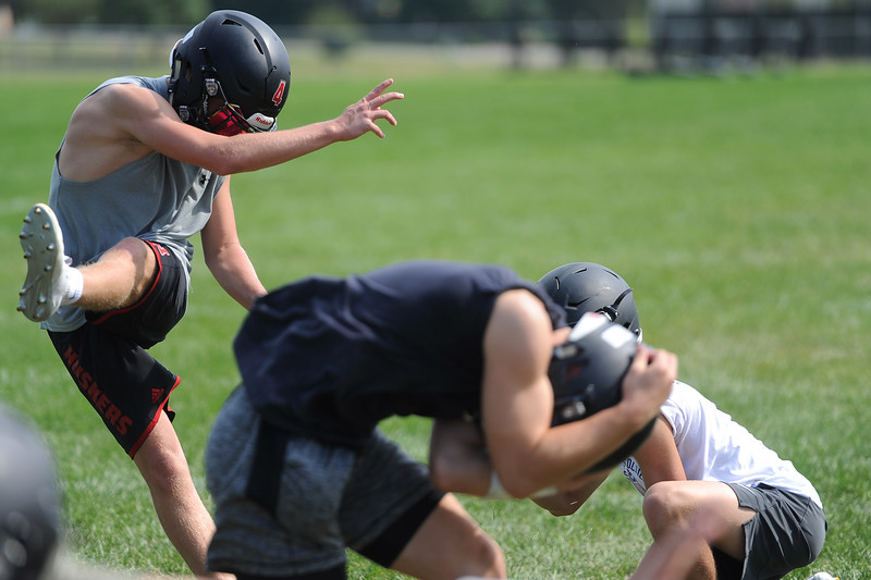 Zach Weinmaster, middle, ducks out of the way of an extra point kick by Cody Rakowsky during the Loveland football team's practice Thursday, Aug, 16, 2018 at Loveland High School. (Sean Star/Loveland Reporter-Herald)