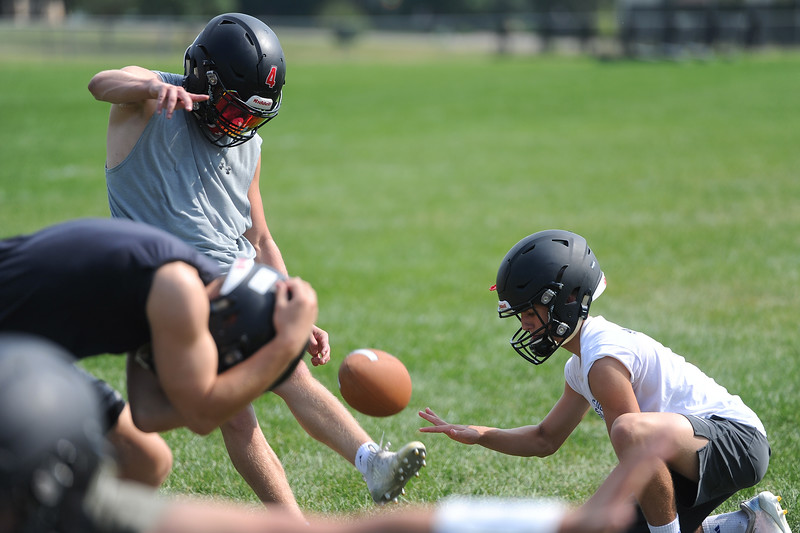 Cody Rakowsky kicks an extra point as his brother, Zack, holds while Zach Weinmaster, lefts, ducks out of the way during the Loveland football team's practice Thursday, Aug, 16, 2018 at Loveland High School. (Sean Star/Loveland Reporter-Herald)