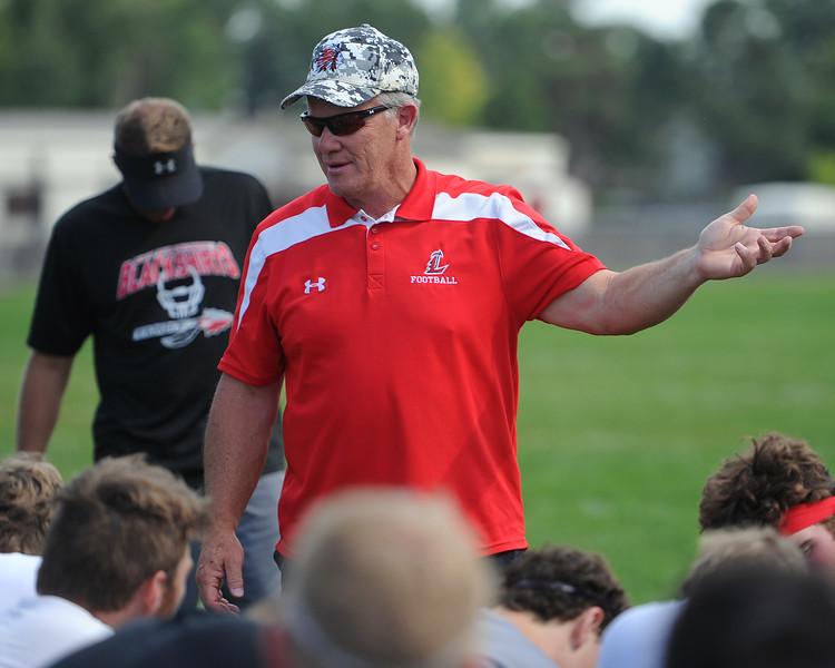 Head coach Wayne McGinn talks after the Loveland football team's practice Thursday, Aug, 16, 2018 at Loveland High School. (Sean Star/Loveland Reporter-Herald)