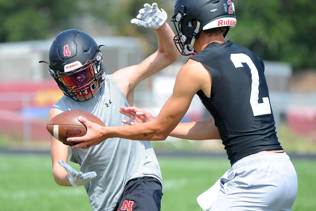 . Cody Rakowsky takes a handoff from Riley Kinney during the Loveland football team�s practice Thursday, Aug. 16, 2018 at Loveland High School. (Sean Star/Loveland Reporter-Herald)