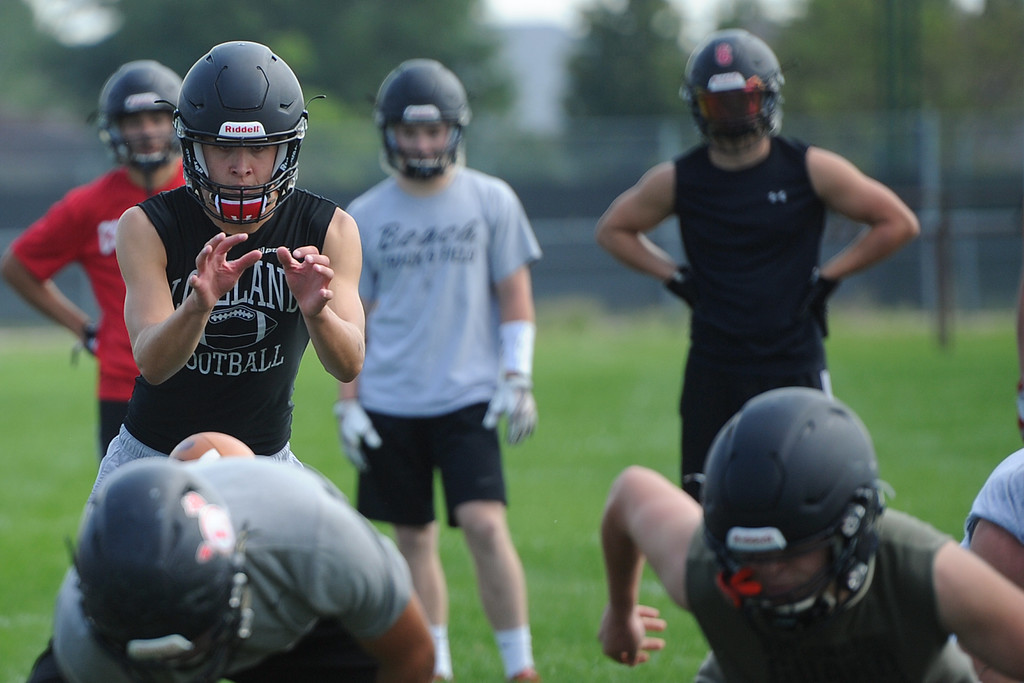 . Riley Kinney takes a snap from the shotgun during the Loveland football team�s practice Thursday, Aug, 16, 2018 at Loveland High School. (Sean Star/Loveland Reporter-Herald)