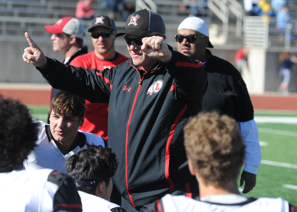 . Loveland head coach Wayne McGinn talks with his team after its win at Greeley West on Saturday.