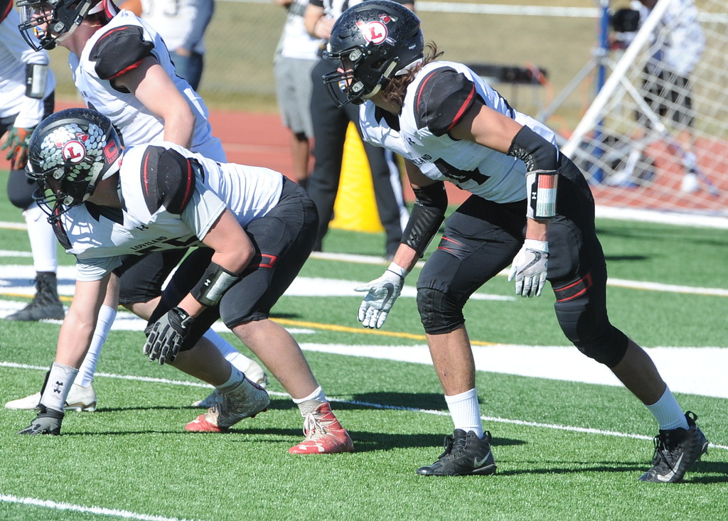 . Loveland defenders Scott Teesdale and Trey Cardenas get ready for a goal-line snap on Saturday at Greeley West.