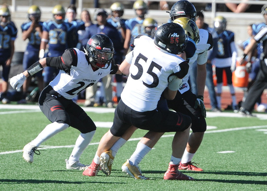 . Loveland\'s Scott Teesdale (55) and Cody Donovan (28) make a tackle on a Greeley West ball carrier on Saturday.