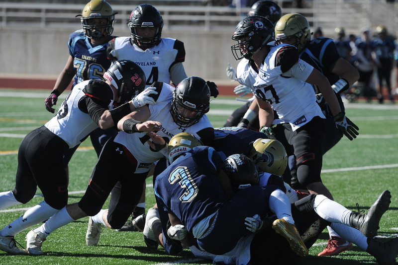 Loveland defenders swarm Greeley West running back Dorrean Starks (3) on Saturday in Greeley.