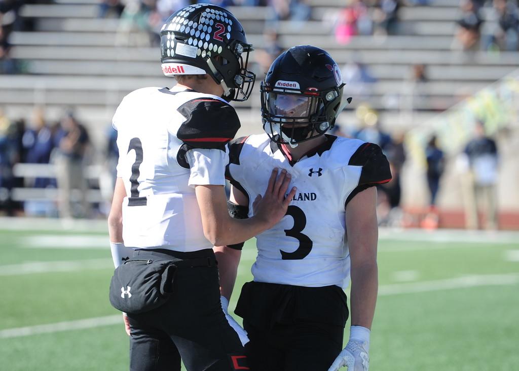 . Loveland quarterback Riley Kinney (2) talks to running back Zach Weinmaster (3) at Greeley West on Saturday.