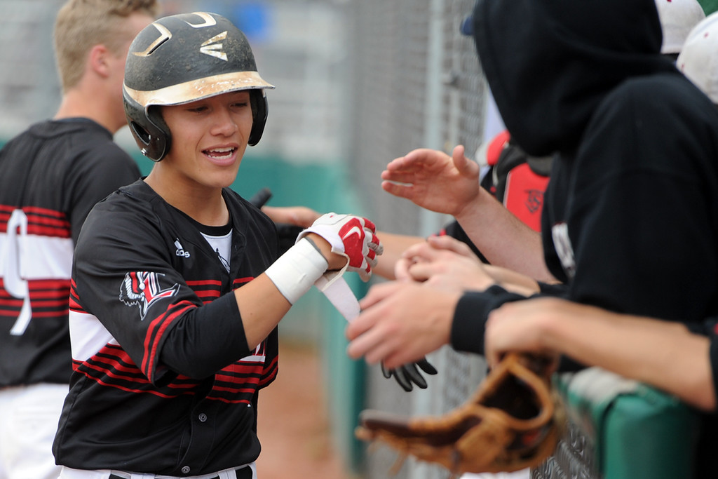 . Loveland\'s Jaxon Cabrera shakes hands with his teammates in the dugout before a 5A regional game at Mountain Range High School on Saturday, May 12, 2018. (Sean Star/Loveland Reporter-Herald)