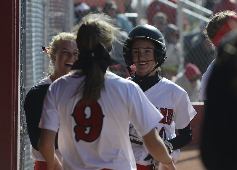 Loveland senior Jessi Case is greeted by teammates in the dugout after scoring the winning run during Saturday's regional title game at Brighton High School.