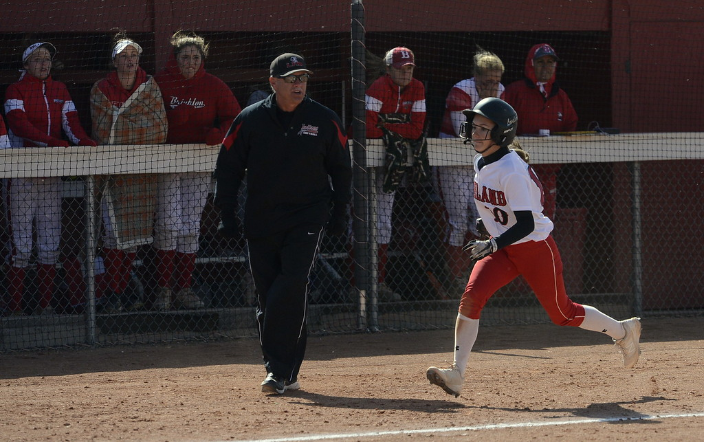 . Loveland coach Mike Felton cheers on Jessi Case as she scores the winning run during Saturday\'s regional title game at Brighton High School.