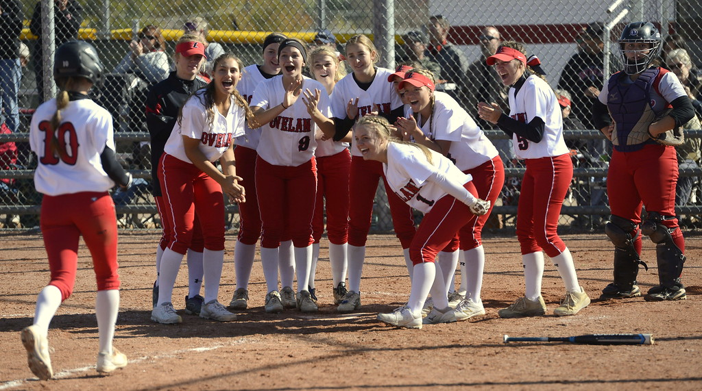 . Loveland softball players wait for senior Jessi Case (10) to touch the plate after hitting a home run during the first game of the 5A Region 8 tournament in Brighton on Saturday.