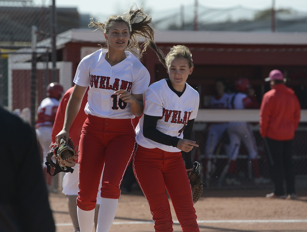 . Loveland\'s Laurin Krings, left, bumps shoulders with teammate Katie McClain on Saturday in Brighton.