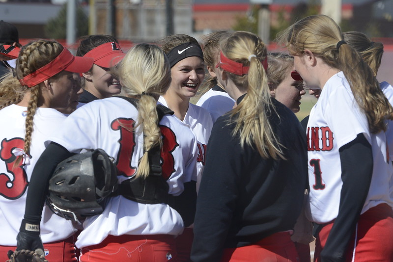 Loveland softball players huddle up between innings on Saturday in Brighton.