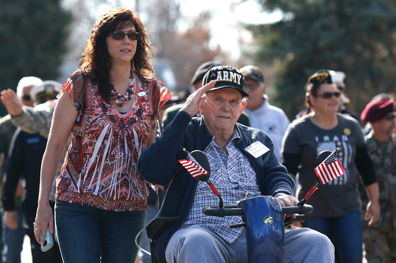Army Veteran Robert Stubblefield salutes the crowd on the parade route along Garfield Avenue with his daughter Carie Audas on Saturday, Nov. 11, 2017, in Loveland. Stubblefield served in France and Germany between the Korean and Vietnam wars. (Photo by Lauren Cordova/Loveland Reporter-Herald)