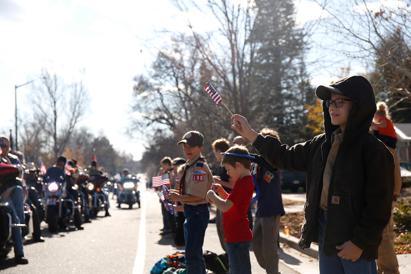 Riley Ramey waves his flag with his troup from cub scouts pack 190 along the parade route on Saturday, Nov. 11, 2017, in Loveland. (Photo by Lauren Cordova/Loveland Reporter-Herald)