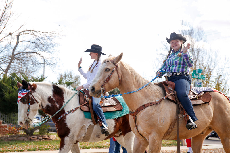 Halley Moak (left) and Amelia Westley wave to the crowds along the Veterans Day parade route riding their horses, Joe and Pony, on Saturday, Nov. 11, 2017,  in Loveland. (Photo by Lauren Cordova/Loveland Reporter-Herald)