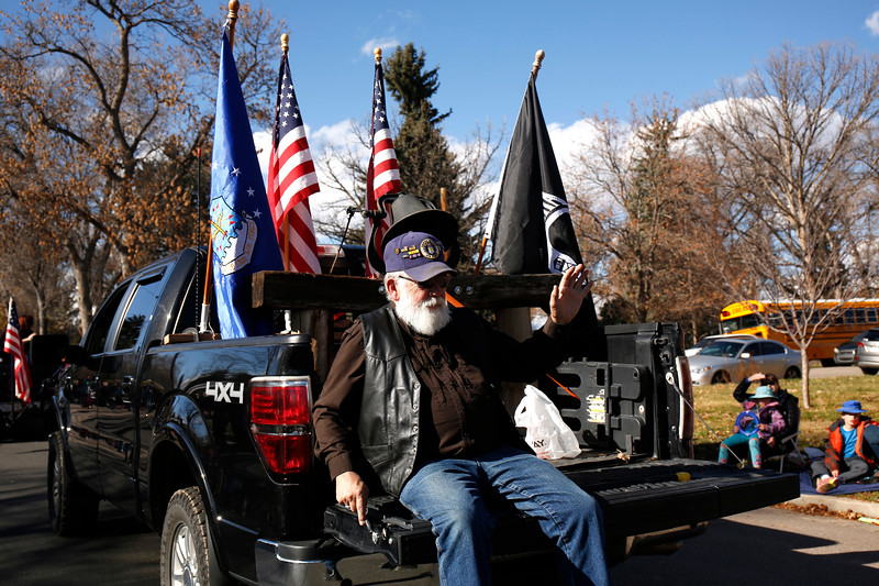 Vietnam Veteran Claude McCormick waves to the crowd along the parade route on 13th street from the back of a truck with a bell ringing behind him right outside of Dwayne Webster Veterans Park on Saturday, Nov. 11, 2017, in Loveland. McCormick served in the Air Force. (Photo by Lauren Cordova/Loveland Reporter-Herald)