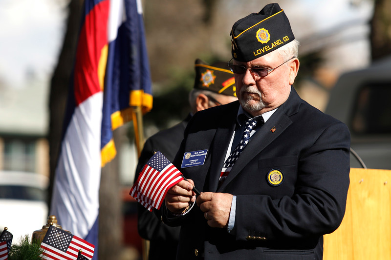 American Legion Commander of post 15 Bart Bartholomew adds flags to a wreath during the roll call of names, honoring fallen veterans, on Saturday, Nov. 11, 2017, at the Veterans Day ceremony at Dwayne Webster Veterans Park in Loveland. (Photo by Lauren Cordova/Loveland Reporter-Herald)