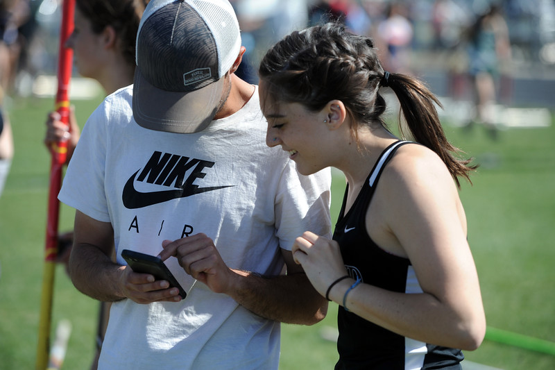 Berthoud pole vaulter Emma Briles, right, looks at a video replay of her vault with district coach Paul Bohannan during the Spartan Spike No. 2 Meet on Thursday at Berthoud High School. (Sean Star/Loveland Reporter-Herald)