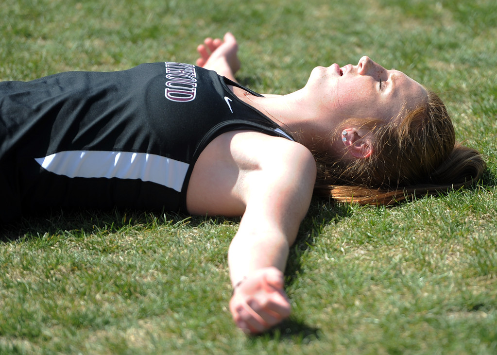 . Berthoud\'s Emily Cavey lays in exhaustion after the 3,200-meter relay during the Spartan Spike No. 2 Meet on Thursday at Berthoud High School. (Sean Star/Loveland Reporter-Herald)