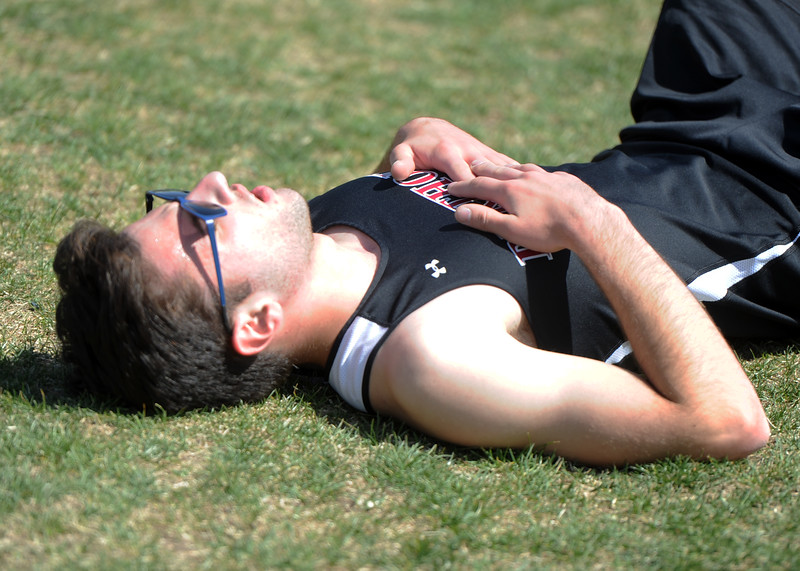 Berthoud's Sergey Eggers lays in exhaustion after the 3,200 during the Spartan Spike No. 2 Meet on Thursday at Berthoud High School. (Sean Star/Loveland Reporter-Herald)
