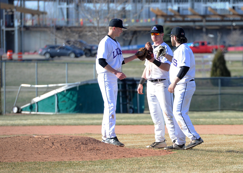 Mountain View baseball players, from left, Anthony Bartelson, Braden Barker and Dakota Jimenez tap gloves before an inning on Tuesday, April 3, 2018 at Brock Field in Loveland. (Sean Star/Loveland Reporter-Herald)