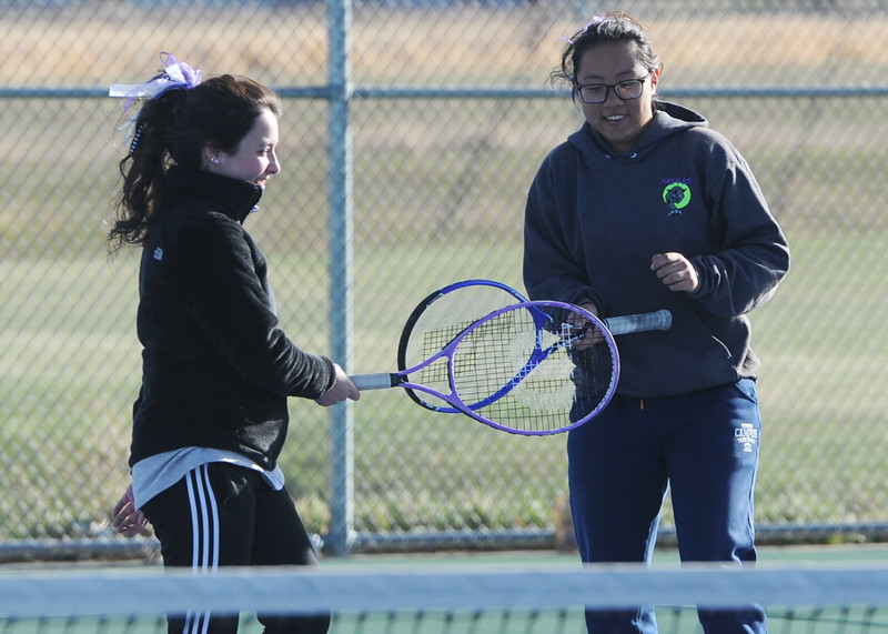 Mountain View teammates Taylor Mills, left, and Angel Yu tap rackets during a match Tuesday, April 3, 2018 at Mountain View High School. (Sean Star/Loveland Reporter-Herald)