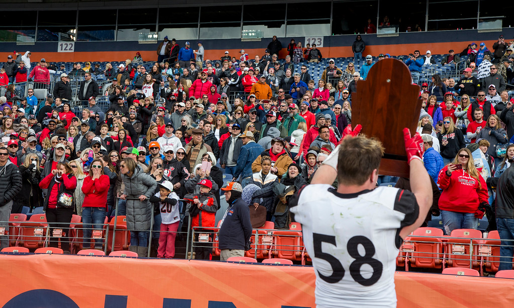 . Loveland\'s Michael Deschene (58) shows the CHSAA 4A State Championship trophy to the crowd following the Indian\'s 62-14 victory over Skyline Saturday afternoon Dec., 1, 2018 at Broncos Stadium in Denver. (Michael Brian/For the Reporter-Herald)