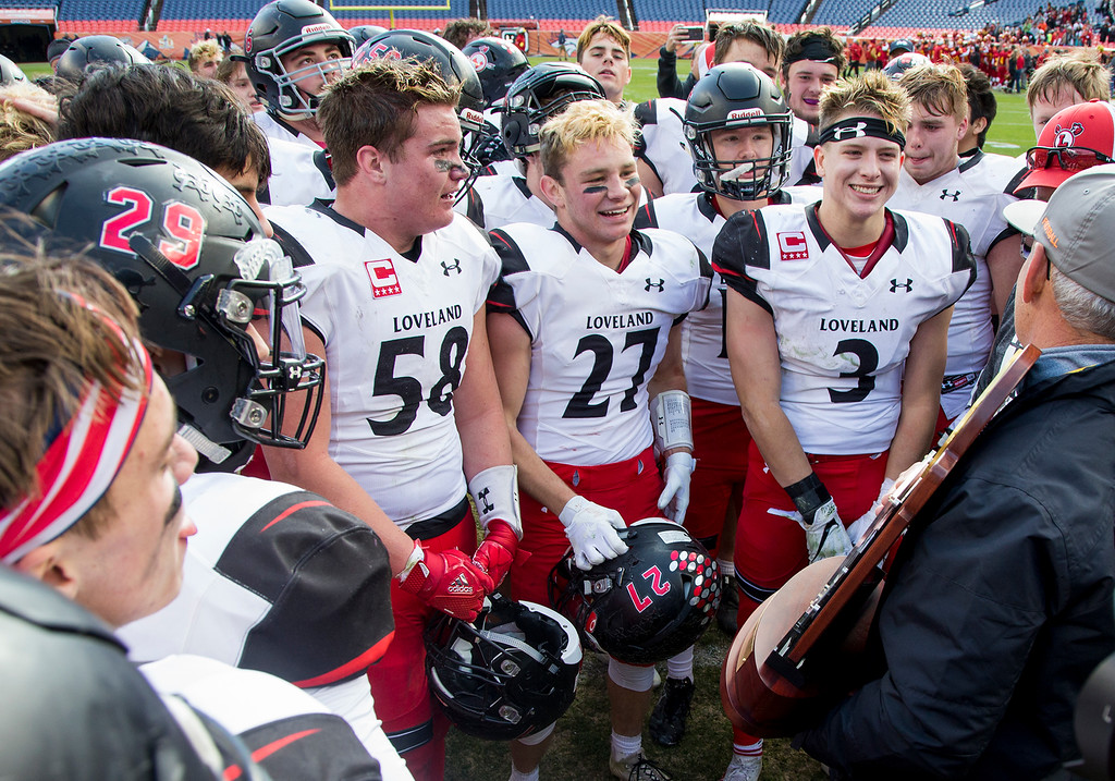 . Loveland Indians players are all smiles as they are presented with the CHSAA 4A State Championship trophy Saturday afternoon Dec., 1, 2018 at Broncos Stadium in Denver after beating the Skyline Falcons 62-14. (Michael Brian/For the Reporter-Herald)
