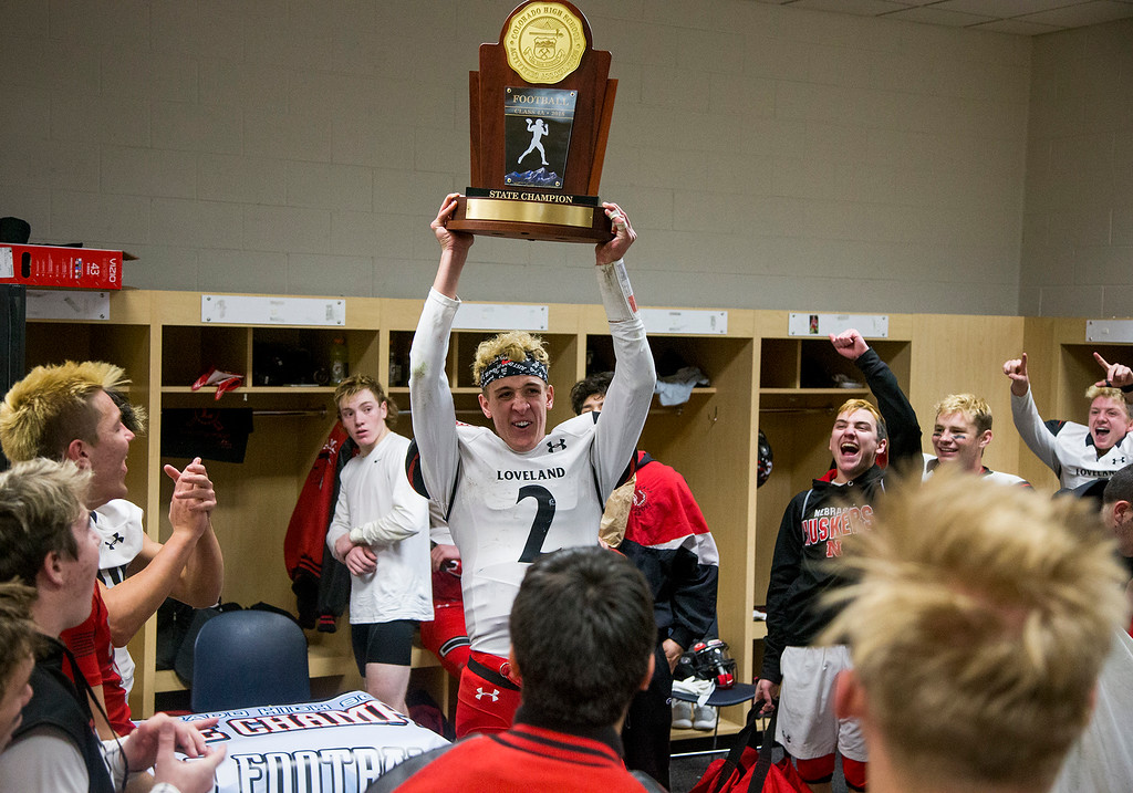 . Quarterback and game MVP Riley Kinney (2) holds the trophy aloft as the Loveland Indians celebrate their 62-14 CHSAA 4A State Championship victory over Skyline Saturday afternoon Dec., 1, 2018 at Broncos Stadium in Denver. (Michael Brian/For the Reporter-Herald)