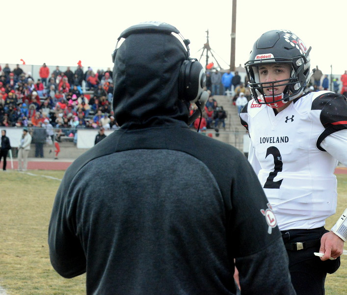 Loveland quarterback gets the playc call from offensive coach Jeff Mauck during Saturday's 4A state semfinal game at Montrose. Loveland won 42-0 to advance to the state championship. (Mike Brohard/Loveland Reporter-Herald)