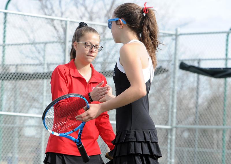 Loveland teammates Aubrey Woodard, left, and Megan Lindsey high-five during a match on Friday, March 30, 2018 at Loveland High School. (Sean Star/Loveland Reporter-Herald)