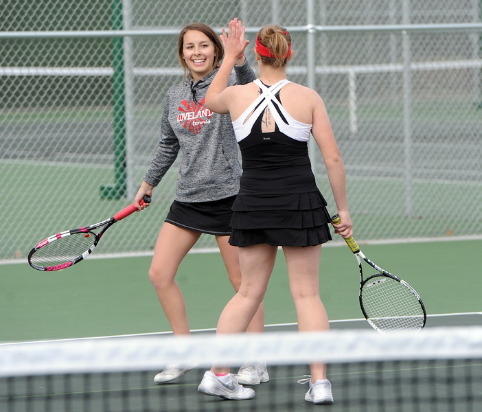 Loveland's Heather Price, left, and Emily Eggerling high-five during their No. 2 doubles match against Mountain View on Friday, March 30, 2018 at Loveland High School. (Sean Star/Loveland Reporter-Herald)
