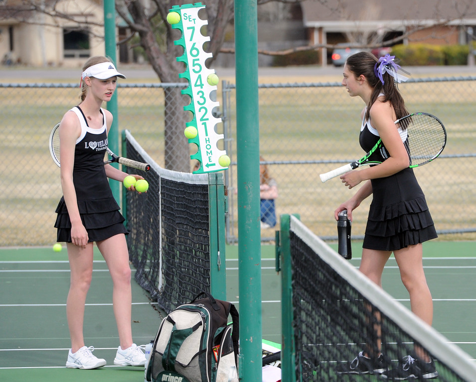 . Loveland\'s Ava McQuade, left, and Mountain View\'s Kendall Krieger take a break between sets during a match on Friday, March 30, 2018 at Loveland High School. (Sean Star/Loveland Reporter-Herald)