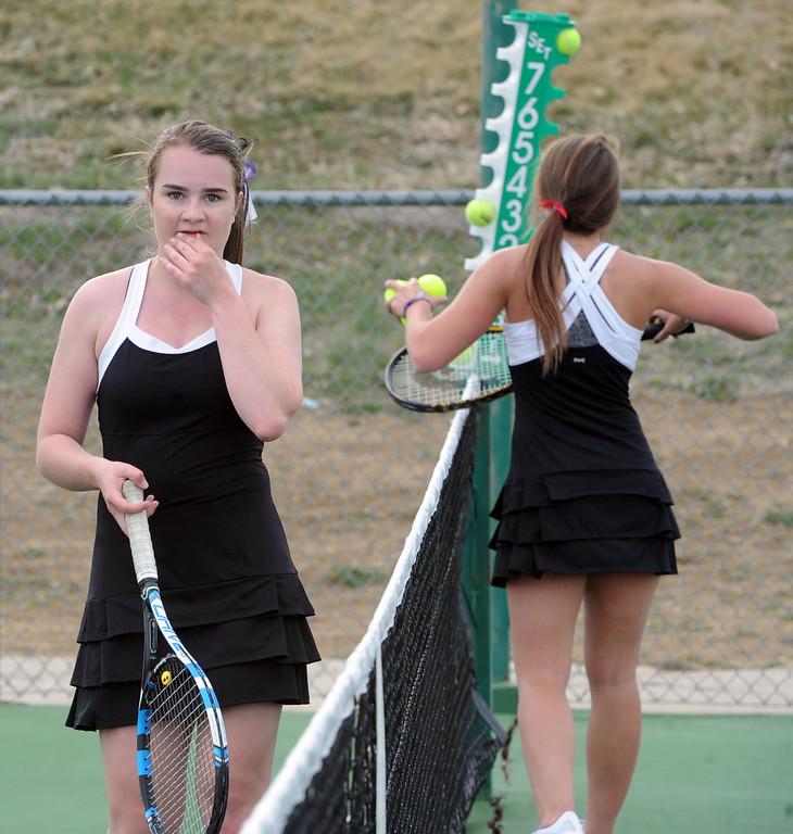 . Mountain View\'s Megan Heesemann, left, and Loveland\'s Kira Badberg take a break between sets during a match on Friday, March 30, 2018 at Loveland High School. (Sean Star/Loveland Reporter-Herald)