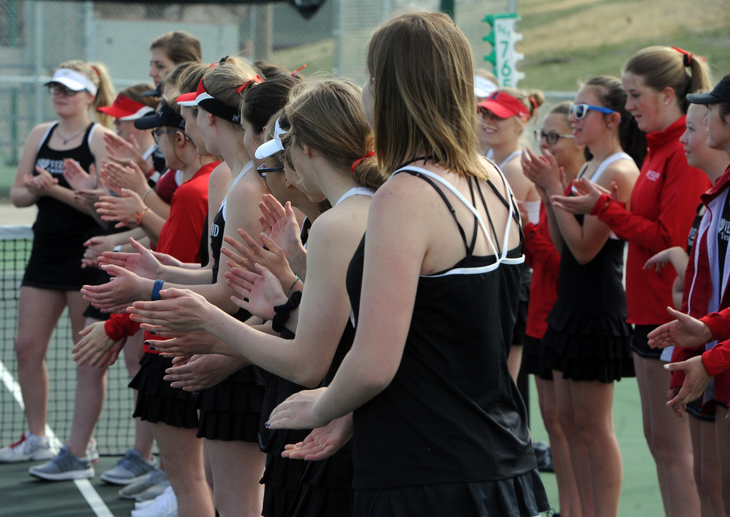 . The Loveland girls tennis team claps during introductions before their match against Mountain View on Friday, March 30, 2018 at Loveland High School. (Sean Star/Loveland Reporter-Herald)